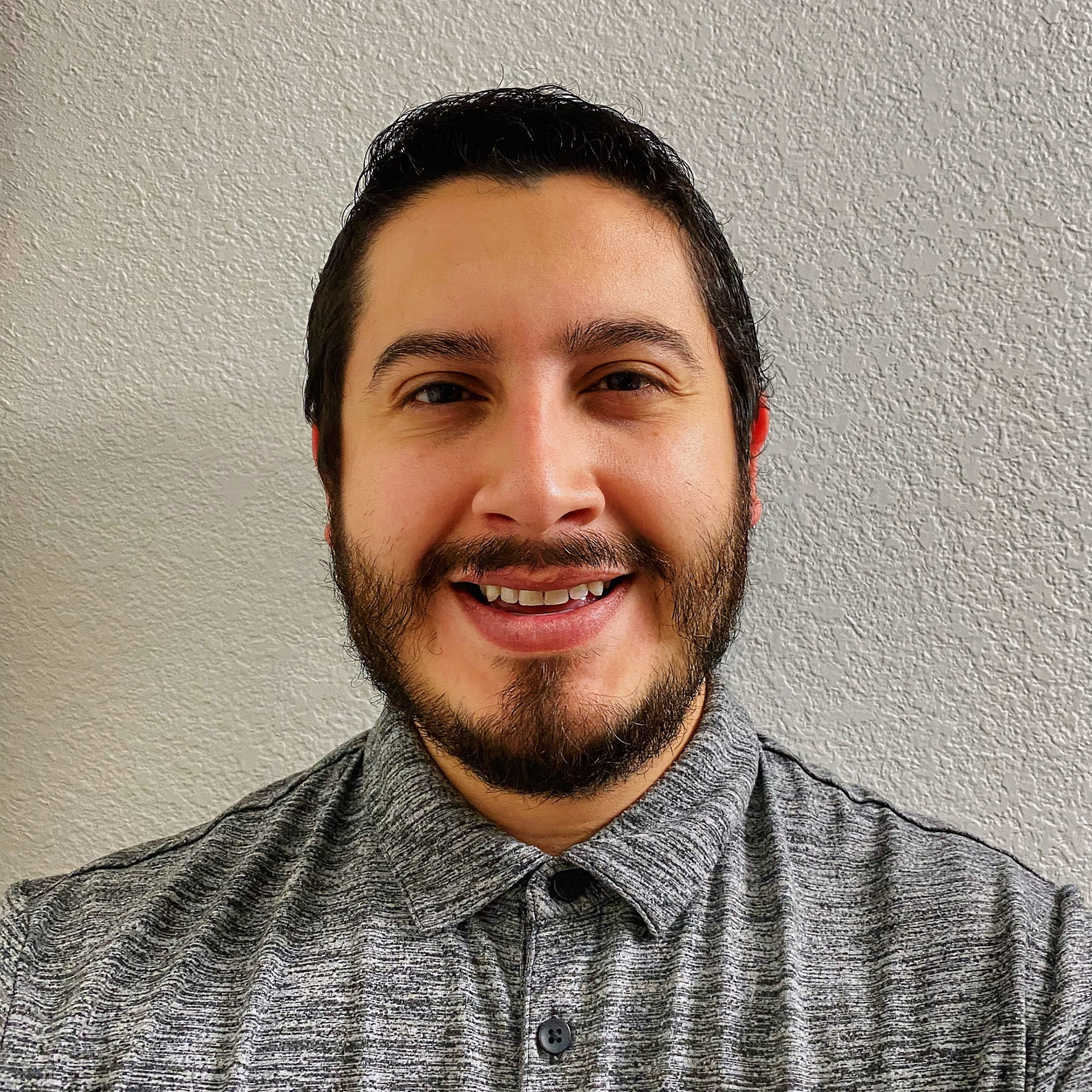 Photo of AT Coordinator Jesse Armijo smiling wearing a gray top in front of a white wall
