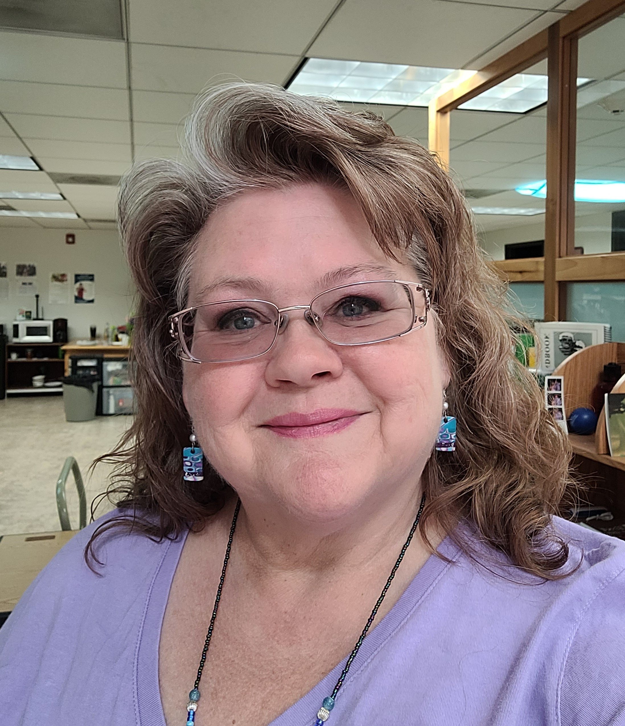 Photo of Program Manager Tracy Agiovlasitis wearing glasses, a purple top, and colorful blue earrings